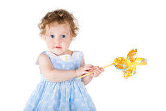 Beautiful little girl playing with a wind toy. On white backgrou Royalty Free Stock Photography