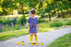 Beautiful little girl of 2 playing with yellow rubber ducks in s Royalty Free Stock Images