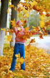 Beautiful little girl plays with autumn leaves Royalty Free Stock Photos