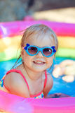 The beautiful little girl in the pool. The beautiful little girl in a bathing suit swims in the pool Royalty Free Stock Photo