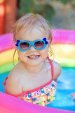 The beautiful little girl in the pool. The beautiful little girl in a bathing suit swims in the pool Royalty Free Stock Image