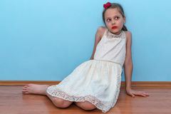 A beautiful little girl poses sitting on the floor stock images