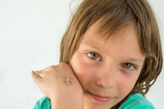 A beautiful little girl poses with a small lizard on her arm.  stock photos