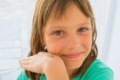 A beautiful little girl poses with a small lizard on her arm.  stock photography