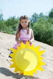 Beautiful little girl posing with paper sun Stock Photo