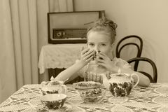 Cute little girl drinking tea at the old table. Stock Image