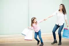 Beautiful little girl pulling mother outside shopping mall. Pretty little hispanic girl with shopping bags pulling mother outside shopping mall Royalty Free Stock Images