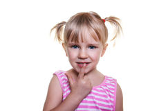 Beautiful little girl putting finger up to lips Royalty Free Stock Images