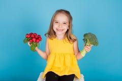Beautiful little girl radishes and broccoli holds food vegetables. Beautiful little girl radishes holds food vegetables stock images