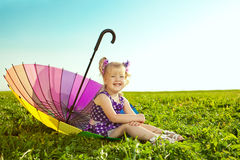 Beautiful little girl with rainbow umbrella on the grass in the Royalty Free Stock Photography
