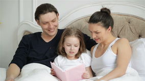 Beautiful Little Girl is Reading Aloud the Book Lying on the Bed with Her Parents. Handsome Father is Kissing His Clever stock video