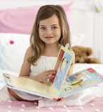 Beautiful little girl reading in bed Royalty Free Stock Photo