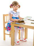 Beautiful little girl reading a book. Stock Images