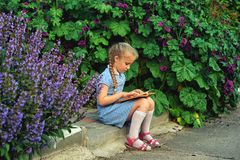 Beautiful little girl holding a book in the street royalty free stock photography