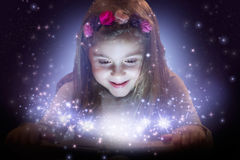 Beautiful little girl reading magic book Stock Photos