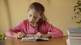 Beautiful little girl reads book stock video