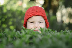 Beautiful little girl, with red cap in green plantations. Girl in the park among the bushes Stock Images