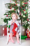 Beautiful little girl in a red dress checking Christmas stocking Royalty Free Stock Photos