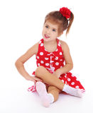 Beautiful little girl in a red dress. Very beautiful little girl with a red bow on her head. The girl dressed in red, summer, short polka dot dress. Girl sitting Royalty Free Stock Photography