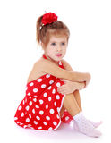 Beautiful little girl in a red dress. Very beautiful little girl with a red bow on her head. The girl dressed in red, summer, short polka dot dress. Girl sitting Stock Photos