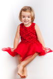 Beautiful little girl in red dresses. Beautiful little girl posing in red dresses royalty free stock images