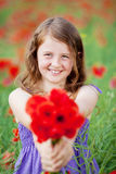 Beautiful little girl with red flowers Royalty Free Stock Photos