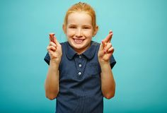 Beautiful little girl with red hair and freckles makes a wish, fingers crossed, believes in fulfillment of dreams, has a stock images