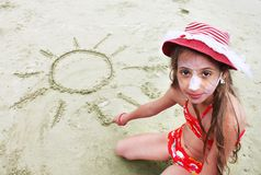 Beautiful little girl with red hat draws the sun in the sand Stock Photo