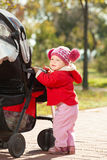 Beautiful little girl in a red jacket on the pram in park Royalty Free Stock Image