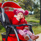 Beautiful little girl in a red jacket on the pram in park Stock Image