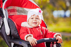 Beautiful little girl in a red jacket on the pram in park Royalty Free Stock Photos