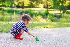 Beautiful little girl in red rain boots playing with rubber frog Stock Images