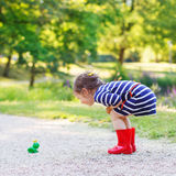 Beautiful little girl in red rain boots playing with rubber frog Royalty Free Stock Photos