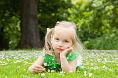 Beautiful little girl relaxing on a meadow royalty free stock image