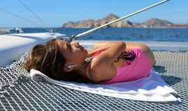 Beautiful little girl relaxing in sailboat while listening to music on the ocean Stock Photo