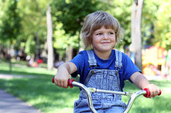 Beautiful little girl rides a bike in the park. Beautiful little blonde girl in denim overalls rides a bike in the park Royalty Free Stock Photo