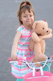 A beautiful little girl is riding a bicycle with a teddy bear. Royalty Free Stock Images