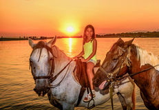Beautiful little girl riding horse in  sunset by the sea on the Royalty Free Stock Photography