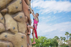 Beautiful little girl rock climbing while on vacation. Cute little girl having fun rock climbing while on vacation at a tropical island resort. Climbing and stock image