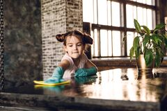 A beautiful little girl in rubber gloves does the cleaning, rags the dust from the table.