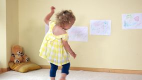 Beautiful little girl running jumping and spinning. Hyperactive child stock footage