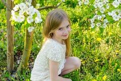 A beautiful little girl runs through a flowering garden in the s Stock Photography