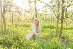 A beautiful little girl runs through a flowering garden in the s Royalty Free Stock Photos