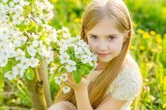 A beautiful little girl runs through a flowering garden in the s Stock Images