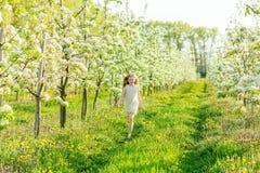 A beautiful little girl runs through a flowering garden in the s Stock Photo