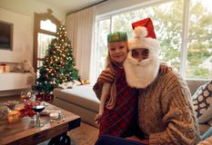 Beautiful little girl with santa claus at home Stock Photos