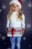 Beautiful little girl in santa hat and jeans smiling and holding a box with Christmas present Stock Images