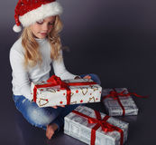 Beautiful little girl in santa hat and jeans smiling and holding Stock Photo