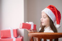 Beautiful little girl in santa hat sitting on chair and holding Royalty Free Stock Images