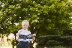 Beautiful little girl seven years old with pigtails in a school. Uniform outdoors, first-grader royalty free stock photography